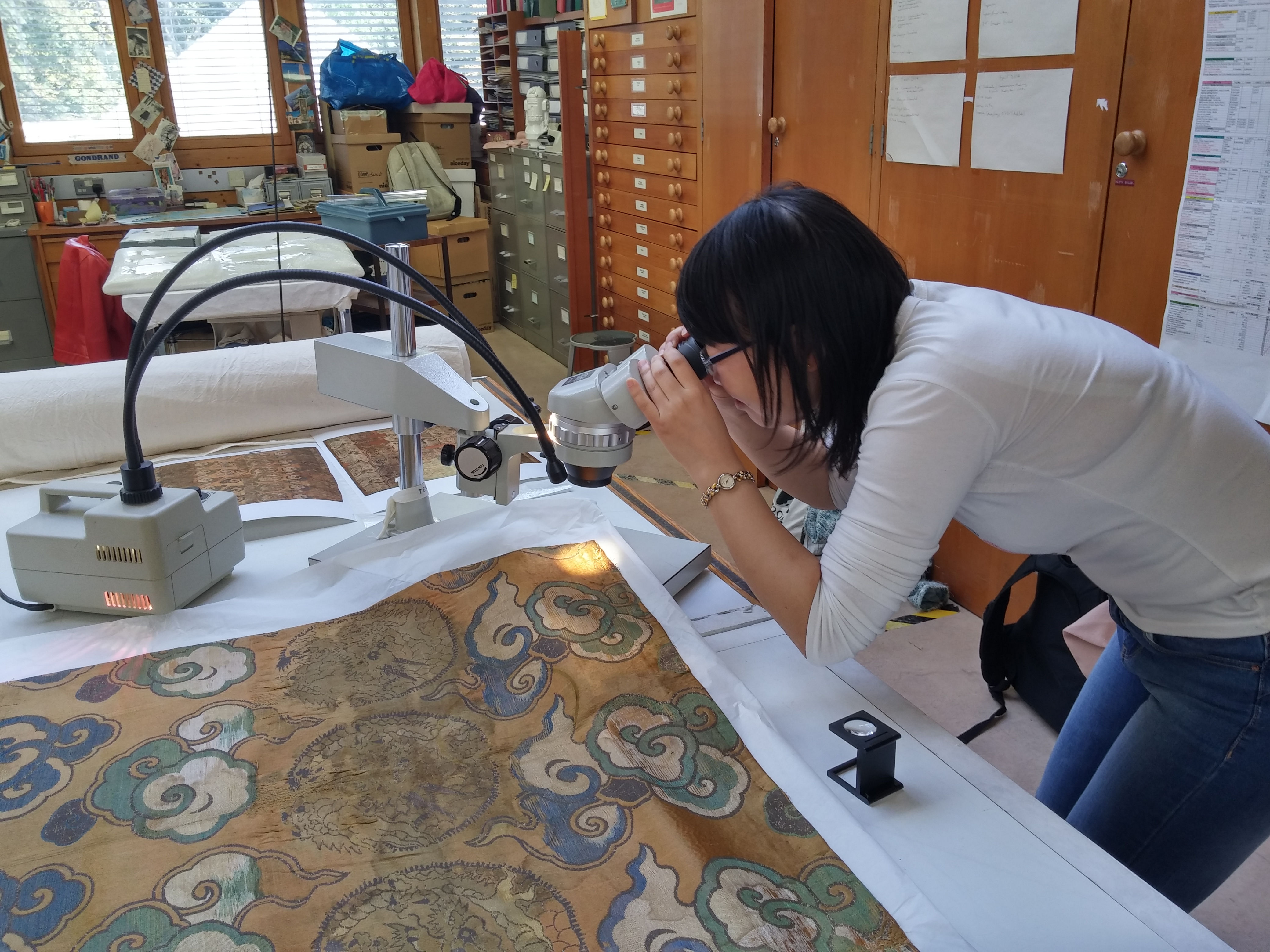 Jing Han examining a Chinese textile in the Glasgow Life collections